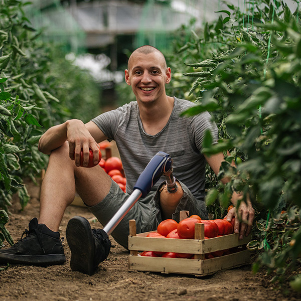 A man who has just picked a crate of tomatoes and who has a prosthetic leg, sits on the ground and smiles