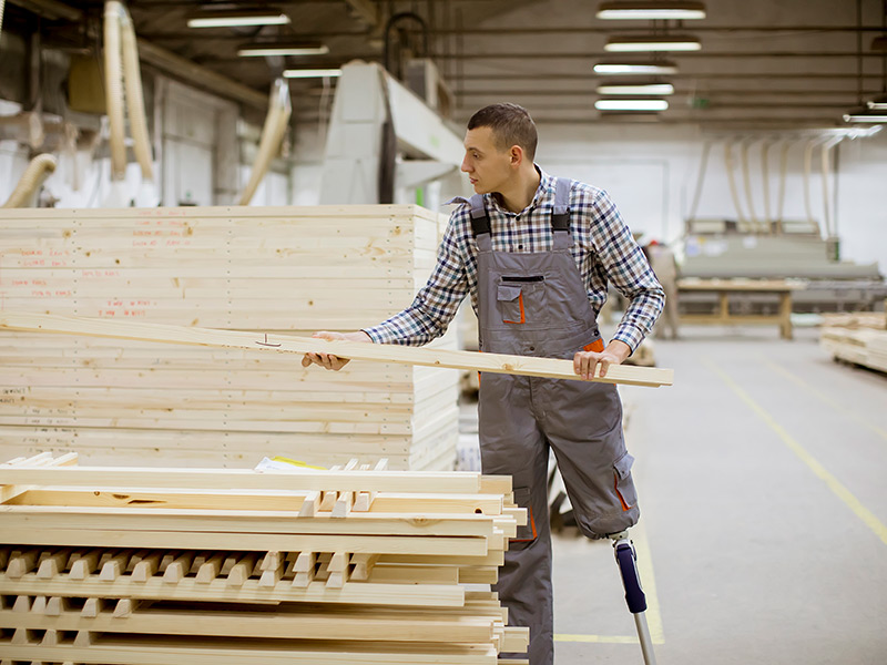 A man who has a prosthetic leg picks up a plank from a pile of planks in a wood shop