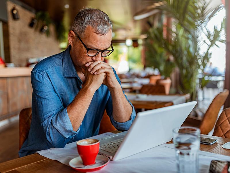 Un hombre se sienta en una mesa de la cocina mientras mira la pantalla de su computadora portátil con una expresión seria en su rostro