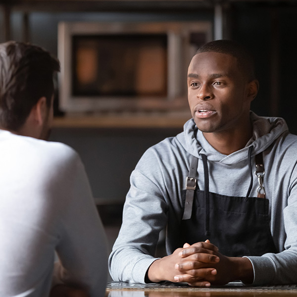 Two men face each other and talk intently. One man is wearing a black kitchen apron over a grey hooded sweatshirt. The other man is wearing a white shirt.