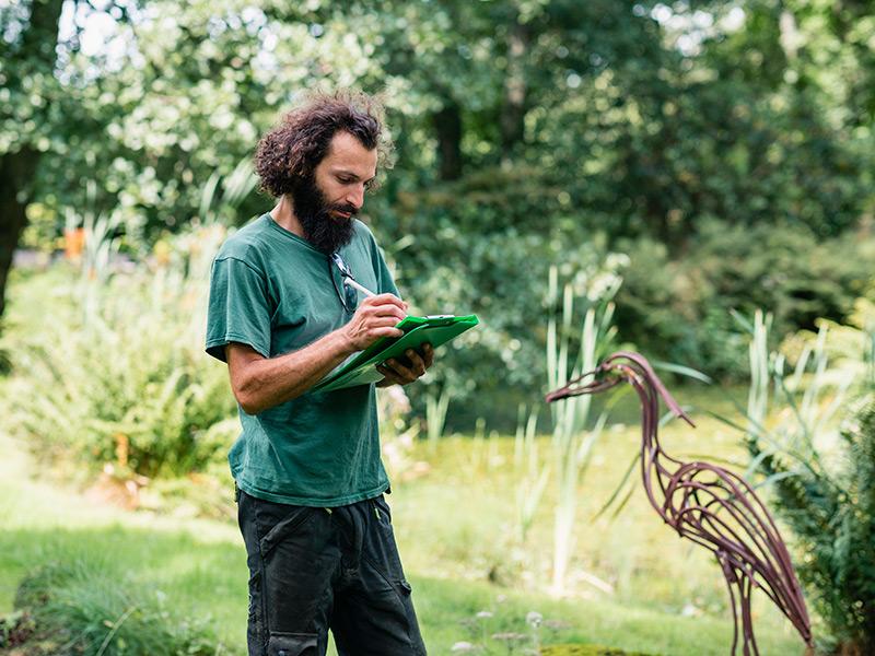 Un arquitecto paisajista toma notas en una libreta mientras está de pie en un jardín