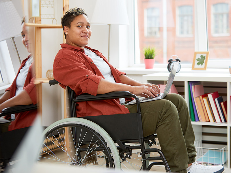 A woman looks up from her laptop, which she is holding on her lap. She is also sitting in a wheelchair, in a professional office setting.
