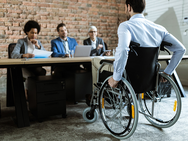 A man in a blue dress shirt and in a wheelchair is being interviewed by three people who sit on the other side of a table from the man