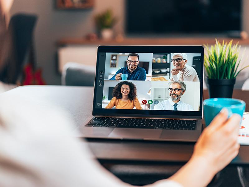 Una persona se sienta en un escritorio mientras mira un chat de video grupal en la pantalla de su computadora