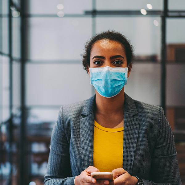 Una mujer con una mascarilla médica mira su teléfono inteligente mientras se prepara para hacer una llamada