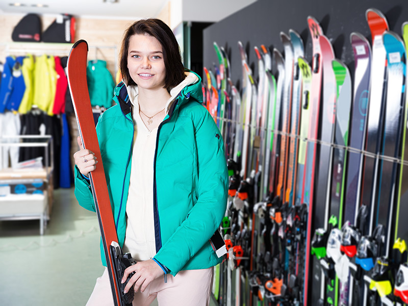 A sales clerk in an outdoor store hold a pair of skis