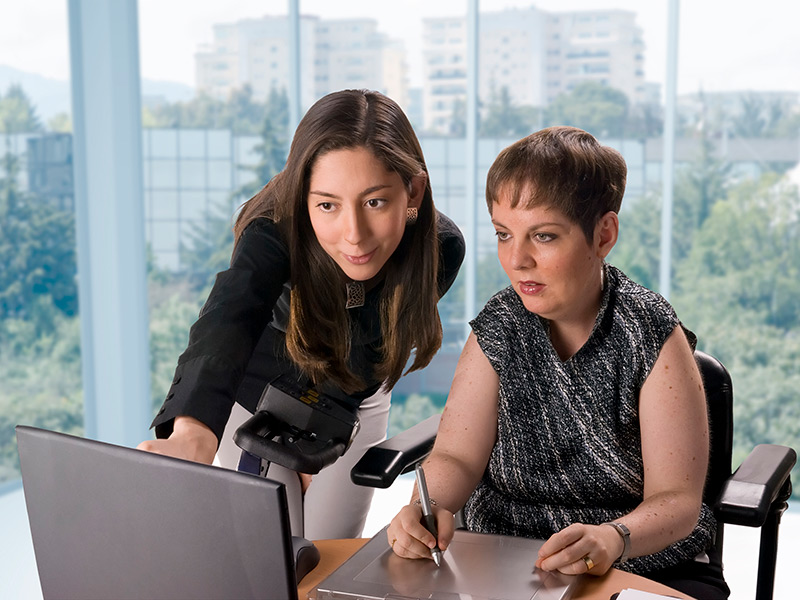 Two women in an office environment work at a computer. One woman is using a stylus as a pointing device on a good-sized trackpad.