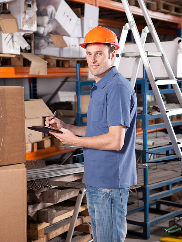 A man wearing a safety helmet writes on a clipboard while standing in front of warehouse shelving