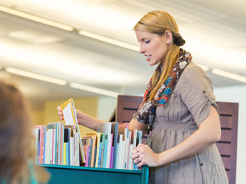 A woman slowly pushes a library book cart with one hand while raising one of the books slightly in order to view the cover