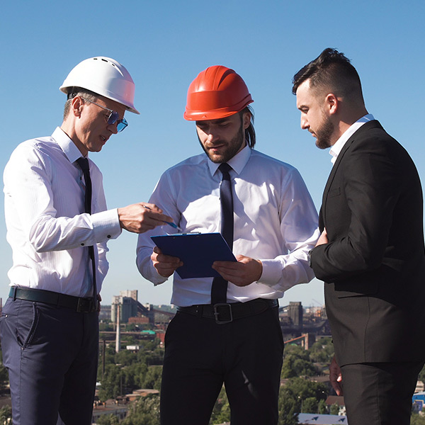 Three men stand outside on a sunny day. Two of them are wearing hard hats. One of them is holding paperwork on a clipboard. All of them are looking at the paperwork.