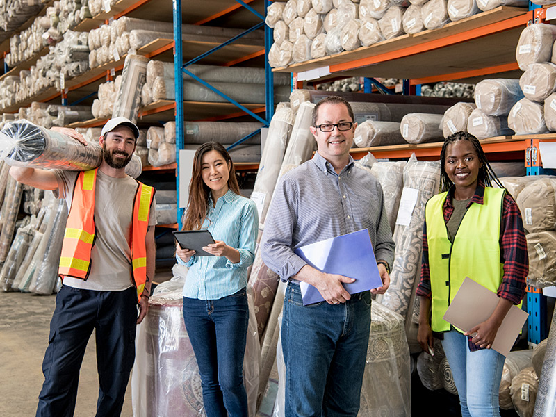 For cheerful workers stand in a warehouse, in front of shelving holding rolls of items that may be carpeting
