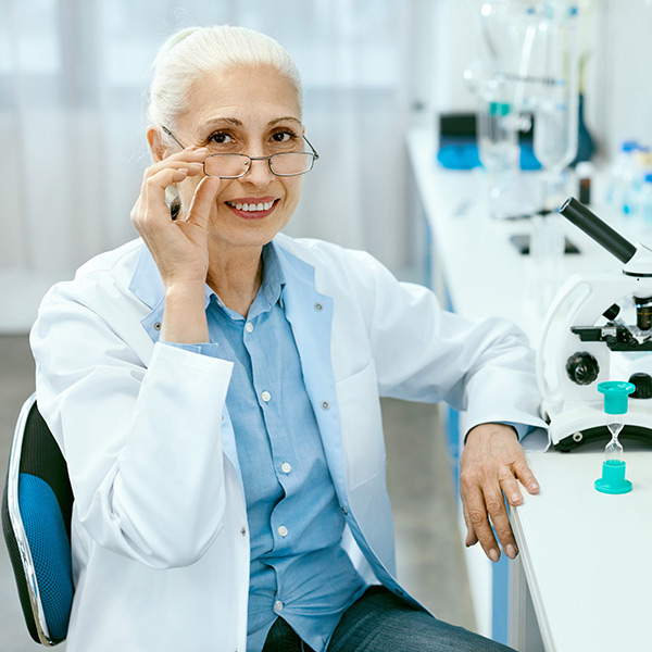 A woman looks up from a lab bench where she is working
